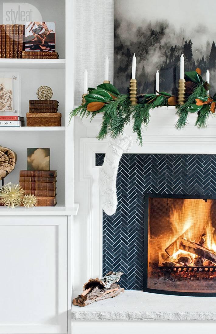 камин с живым огнем украсили сапогом для подарком и свечами