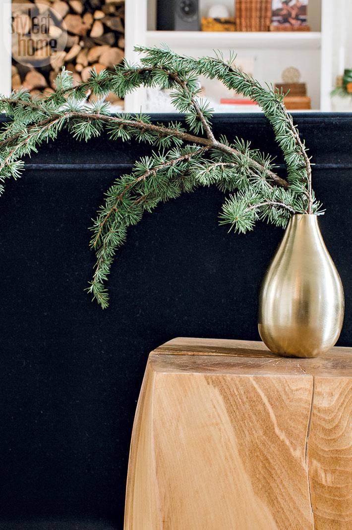 ветка ели в золотой вазе на деревянной подставке в доме