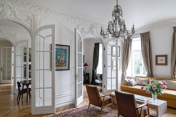 белый интерьер кварттиры с лепниной и распашными дверями