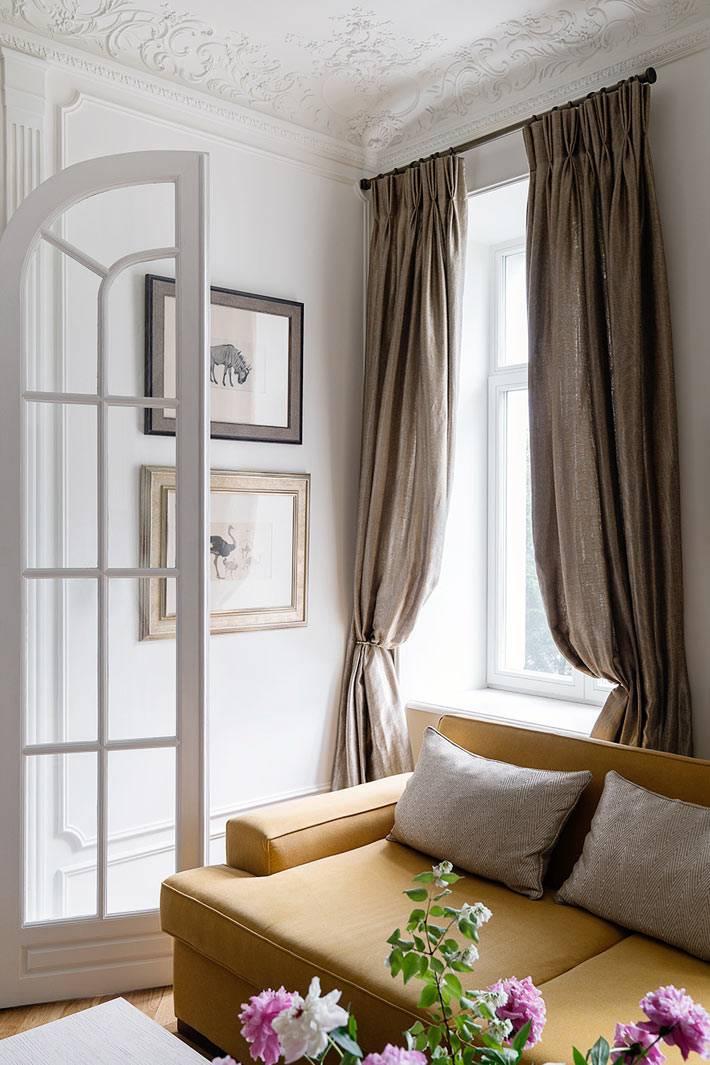 стилизованый диван желтого цвета в интерьере гостиной