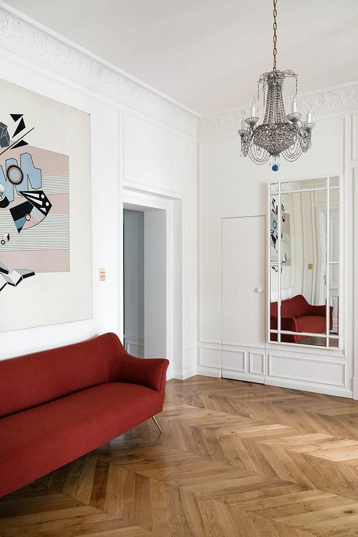 в холле квартиры стоит красный ретро-диван фото