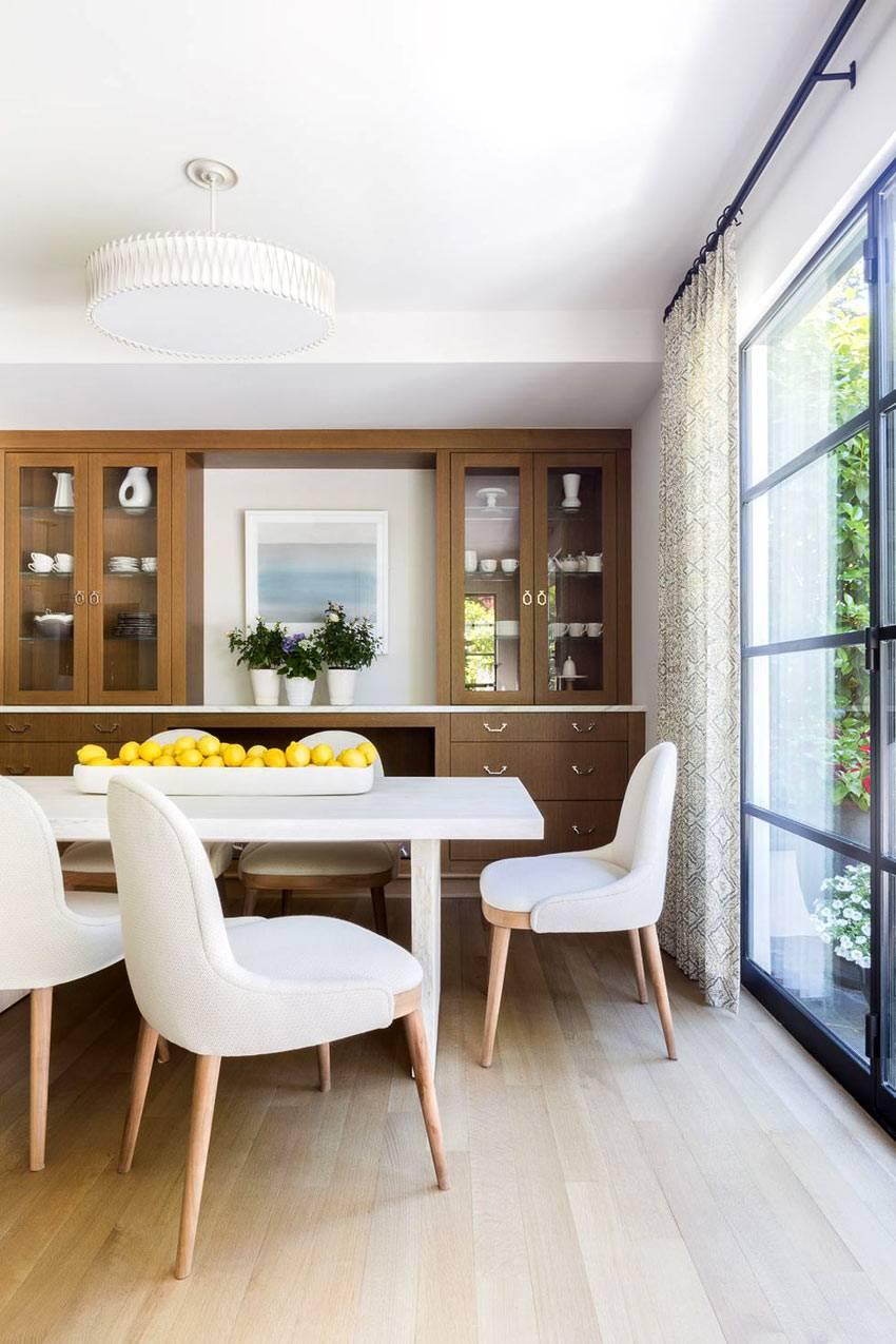 белая столовая группа и коричневый шкаф в столовой зоне