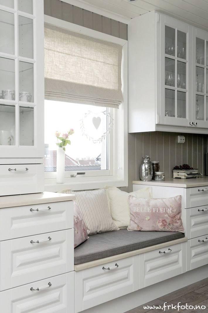 мягкий матрас с подушками на подоконной лавке на кухне
