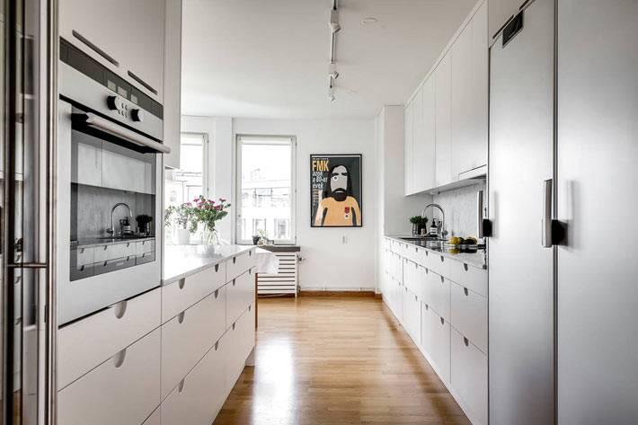 большая кухня с белой мебелью с множеством ящиков