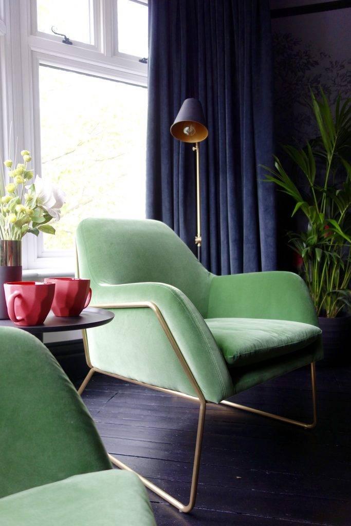 стильное зеленое кресло с металлическим корпусом в спальне