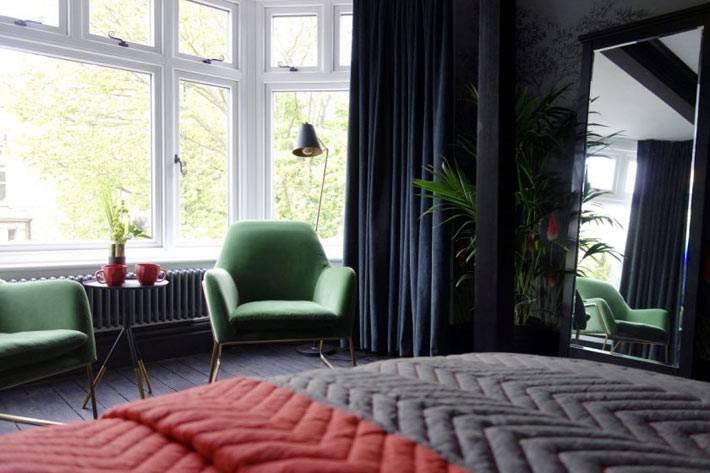 спальня с черной мебелью и большим окном