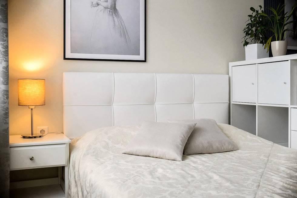 белая кровать с мягким изголовьем и картина с балериной