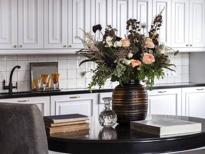 белая кухонная мебель и черный обеденный стол фото
