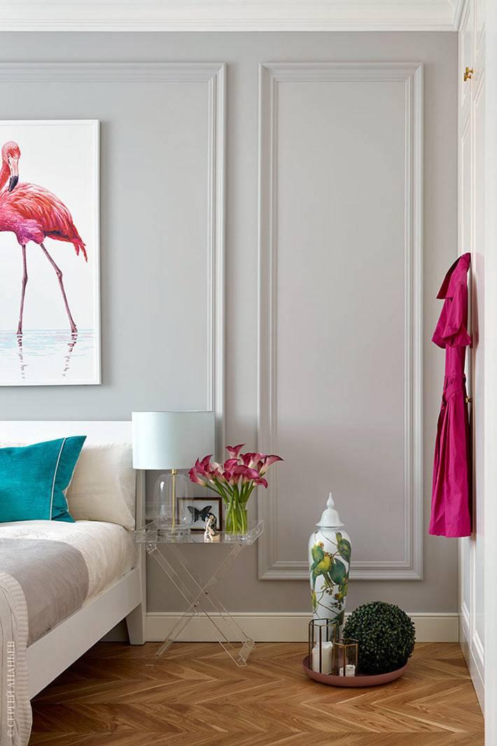 картина с розовым фламинго над кроватью в спальне