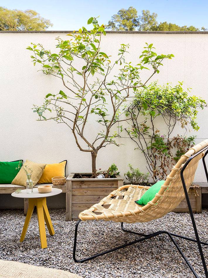 зона отдыха во дворе дома с плетеными креслами