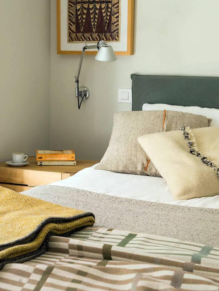 возле кровати над тумбой настенный светильник для чтения