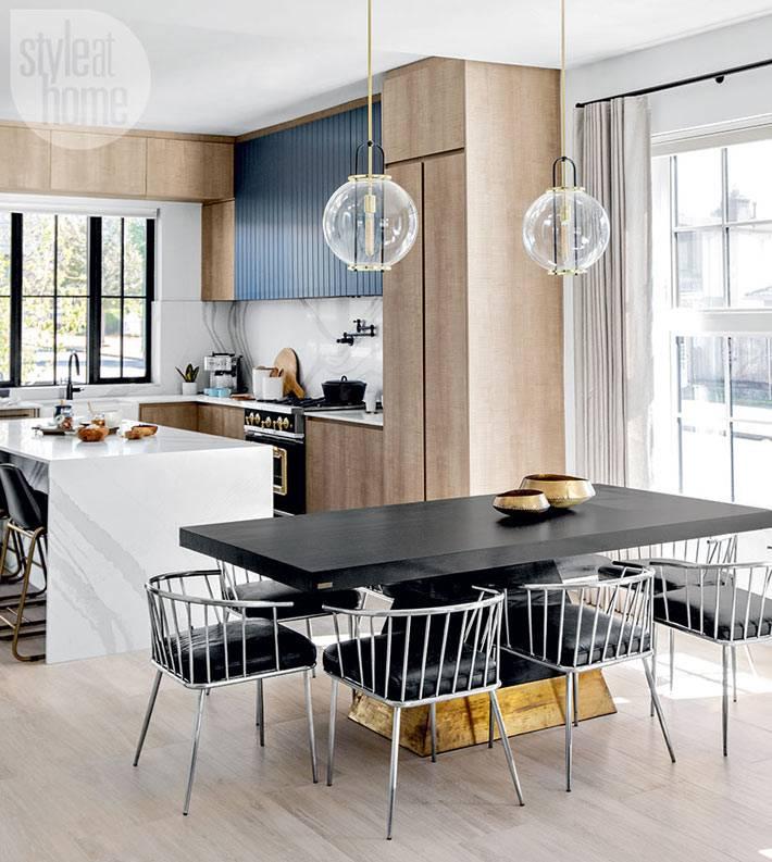 массивный черный стол на кухне с прозрачными светильниками