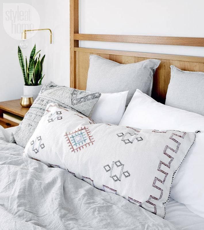 деревянная кровать в спальне и серое постельное белье фото