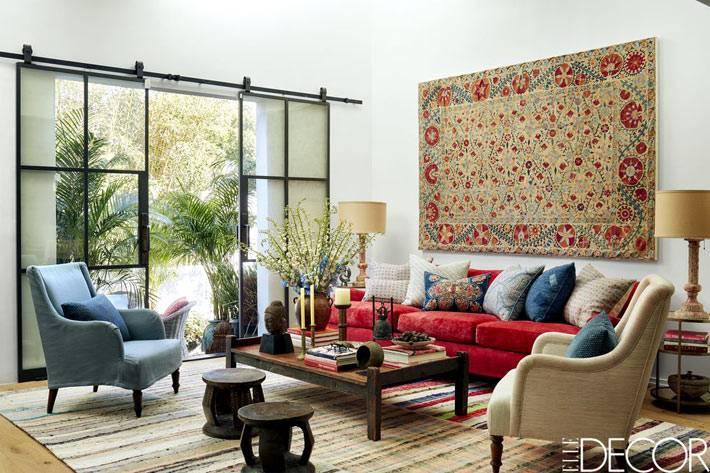 марокканские мотивы в интерьере гостиной с ковром на стене