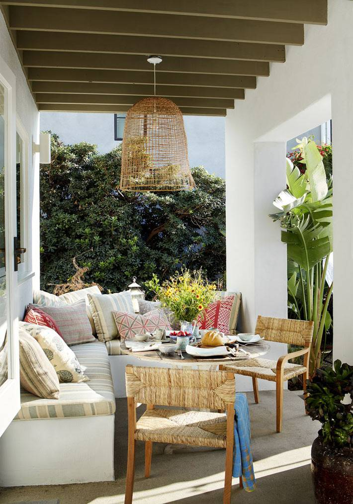 веранда возле дома как место для отдыха с подушками