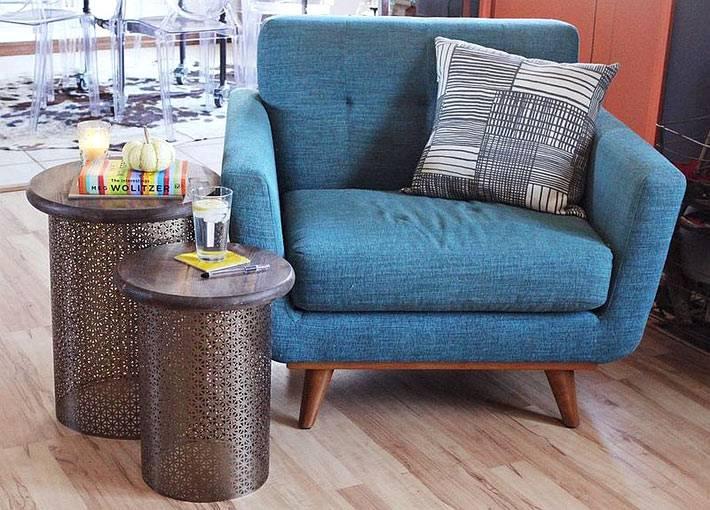 пара столиков с ажурным основанием возле кресла