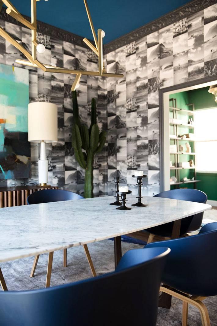 мраморный стол, синие стулья и черно-белые обои в столовой