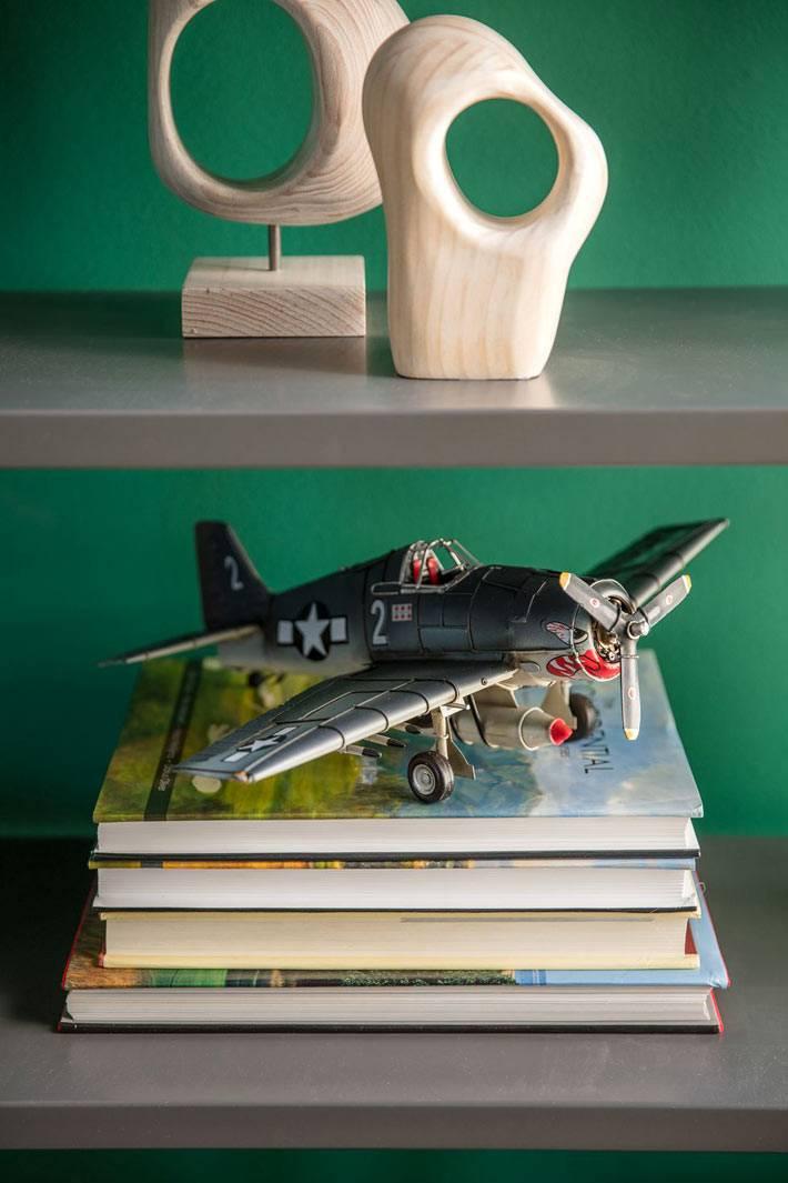 фигурки-декор из дерева и модель самолета на полках стеллажа