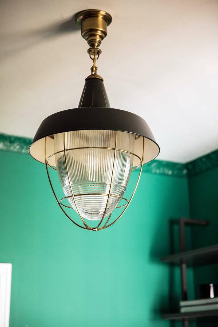 зеленый интерьер комнаты с черной металлической люстрой