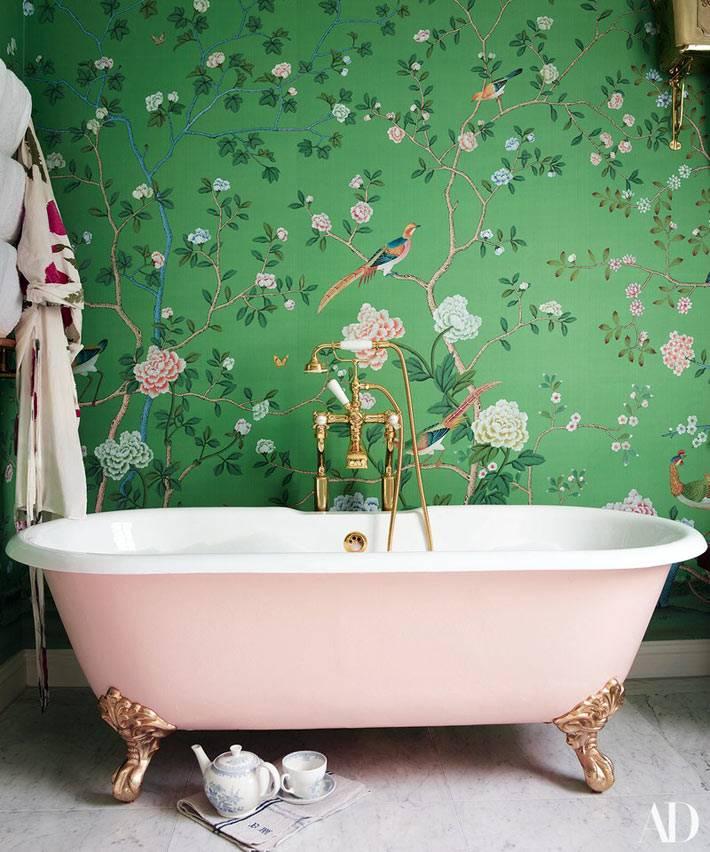 розовая ванна на ножках на фоне зеленой стены с обоями