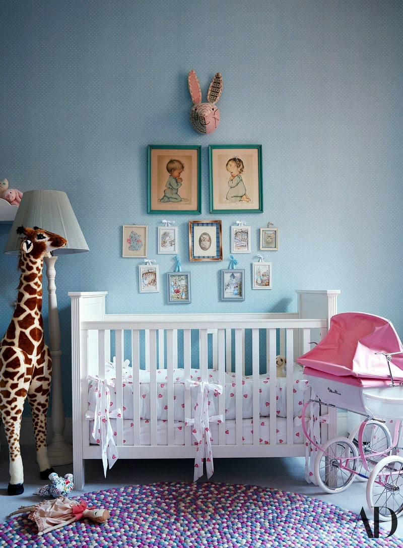 маленькие картинки над белой детской кроваткой и жираф