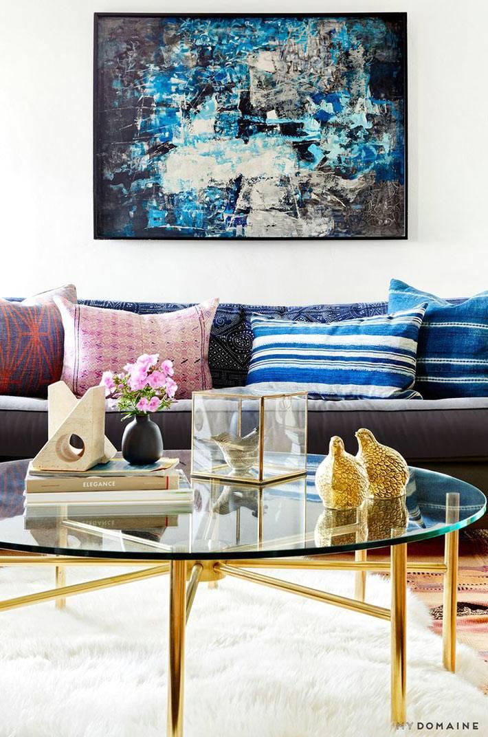 диванные подушки и золотые аксессуары в дизайне гостиной комнаты