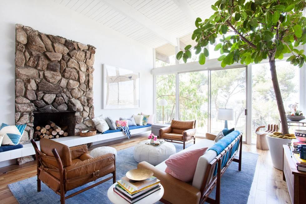 фикусы и природные материалы в комнате с большими окнами в пол