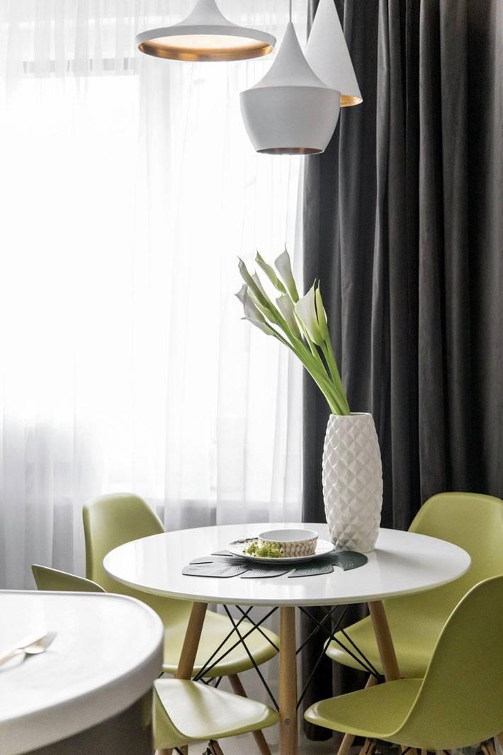 обеденный стол круглой формы с зелеными стульями