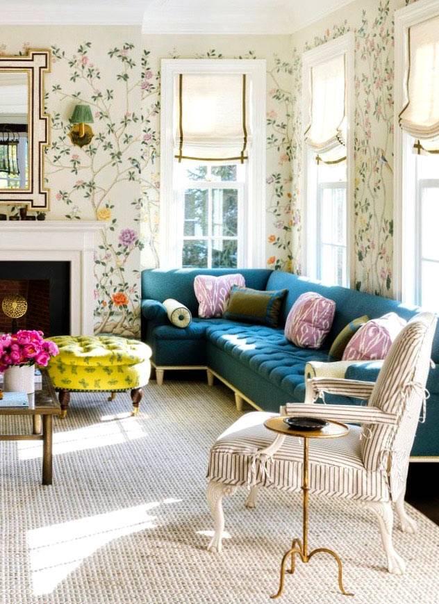 синий угловой диван с подушками в нежном интерьере гостиной