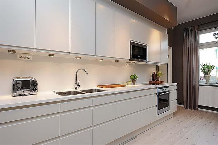 Контрастная белая кухня в черном интерьере квартиры фото