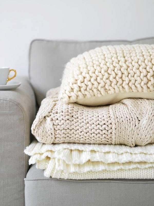 белые вязаные подушки и пледы, зимний интерьер дома