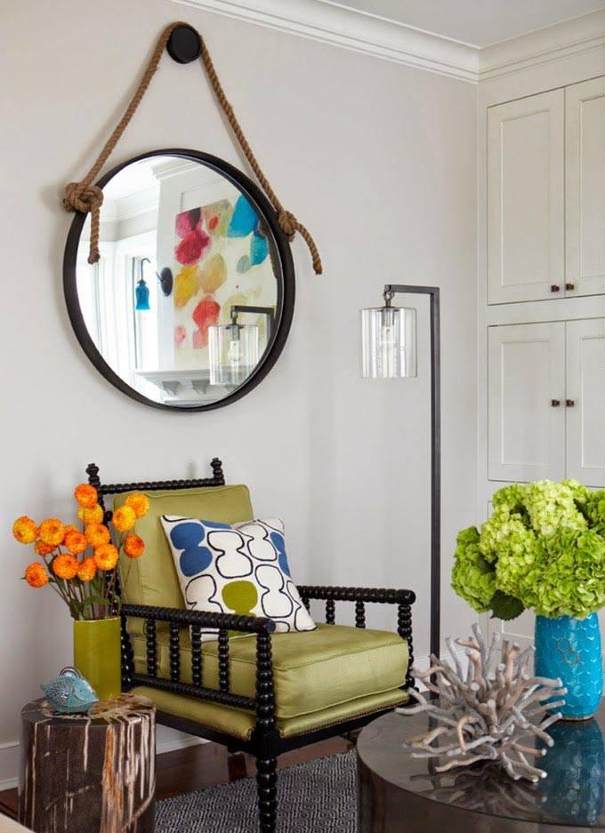 зеленое кресло и круглое зеркало на веревке в прихожей