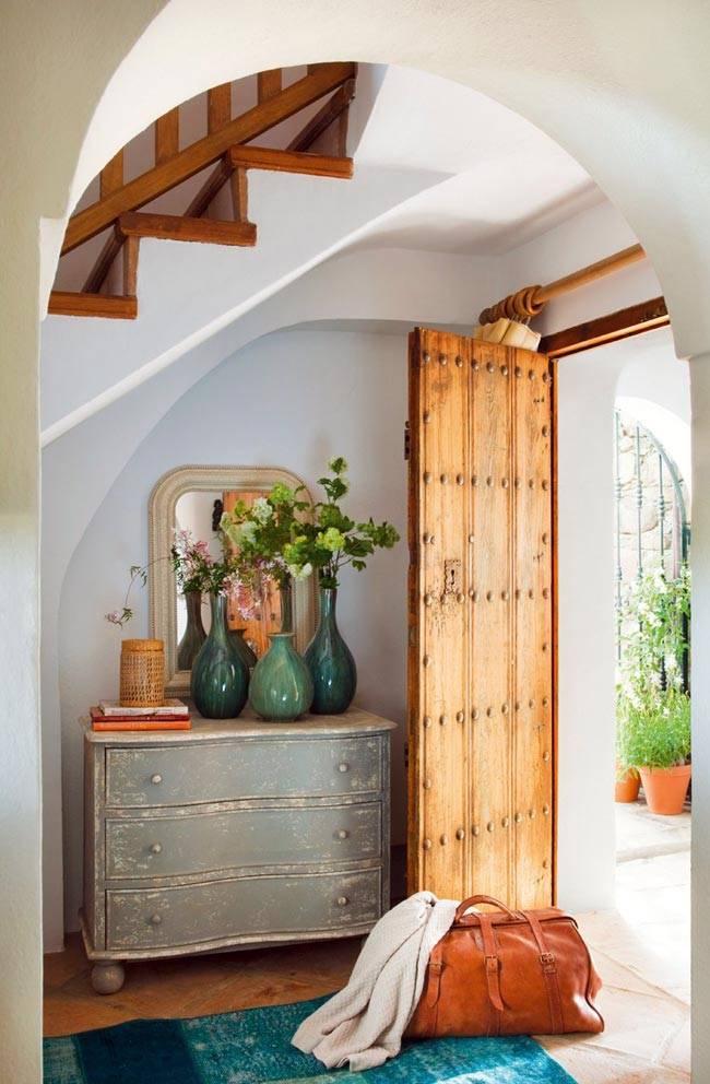 арочный вход в прихожей дома, зелёные вазы на старинном комоде