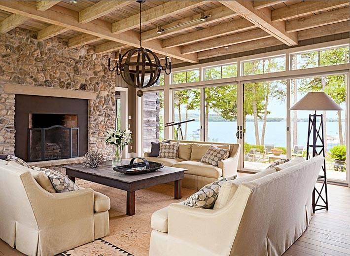 панорамные окна и каменная стена возле камина в доме