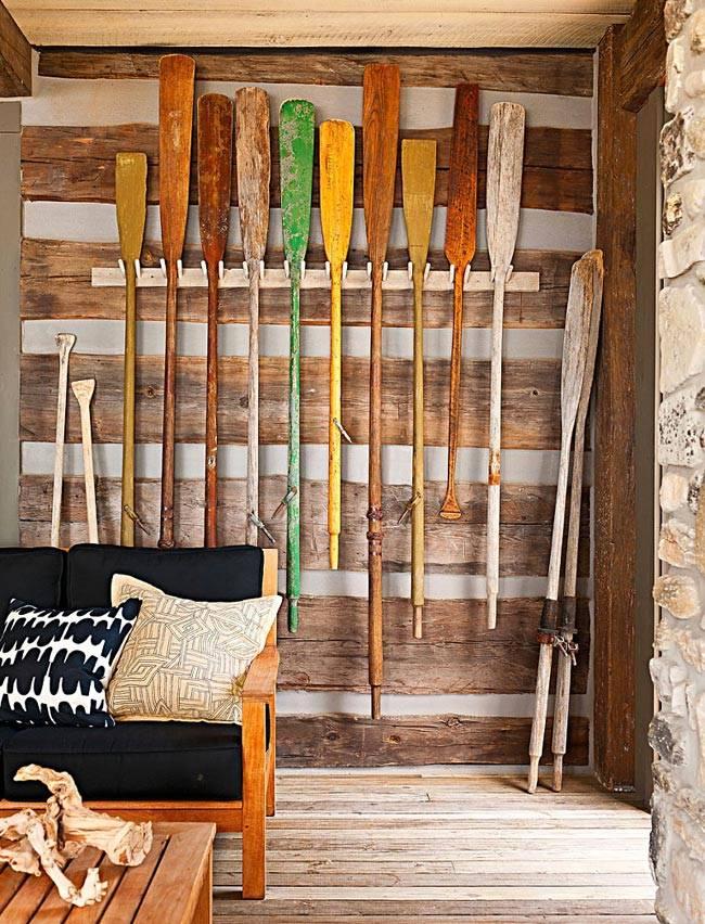 Разноцветные вёсла - необычный декор на стене загородного дома