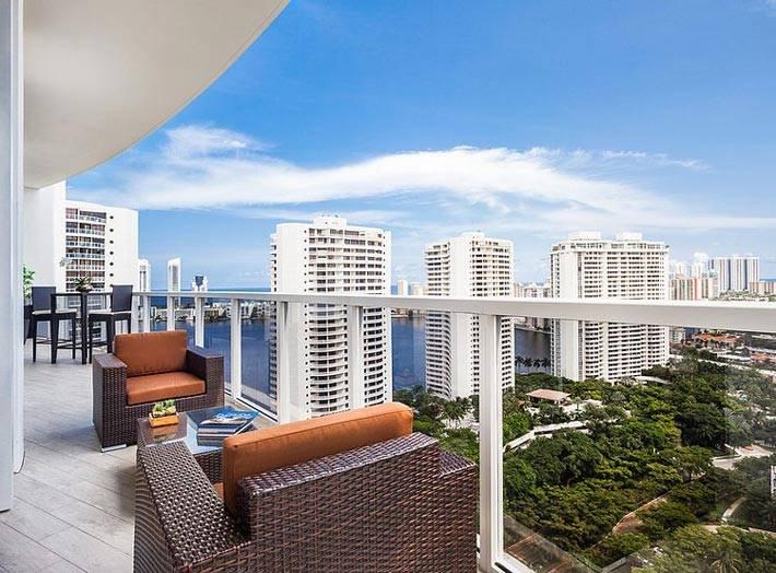 Балкон со стеклянными бортиками с прекрасным видом на город и море