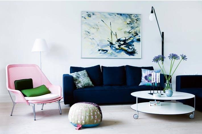 современная гостиная с синим диваном, розовым креслом и круглым белым столиком