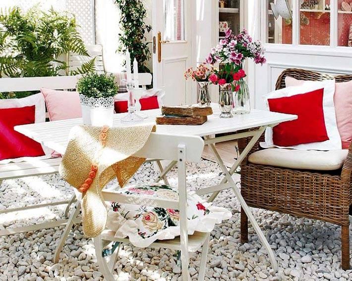 белый стул с подушкой и столик на террасе, пол из мелкой гальки
