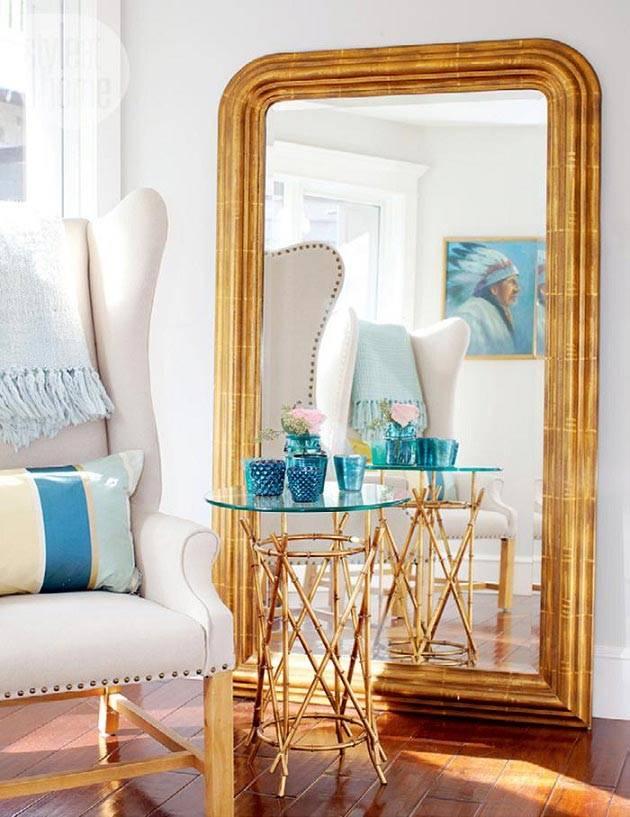 большое зеркало в золотистой раме на полу в гостиной