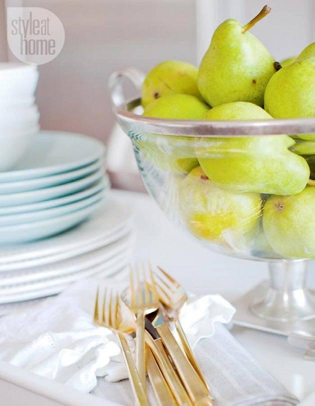 груши в стеклянной сервировочной вазе на столе