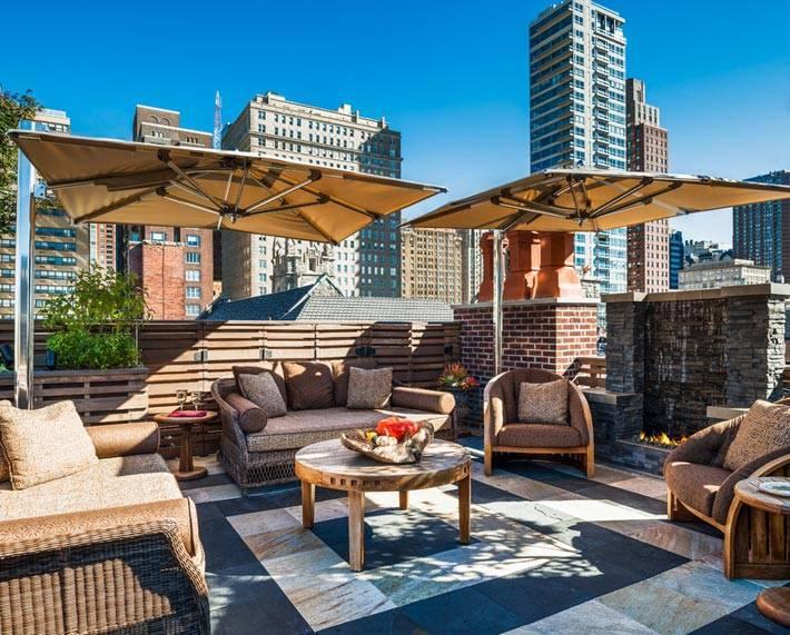 кресла и зонтики от солнца на большом балконе в городе