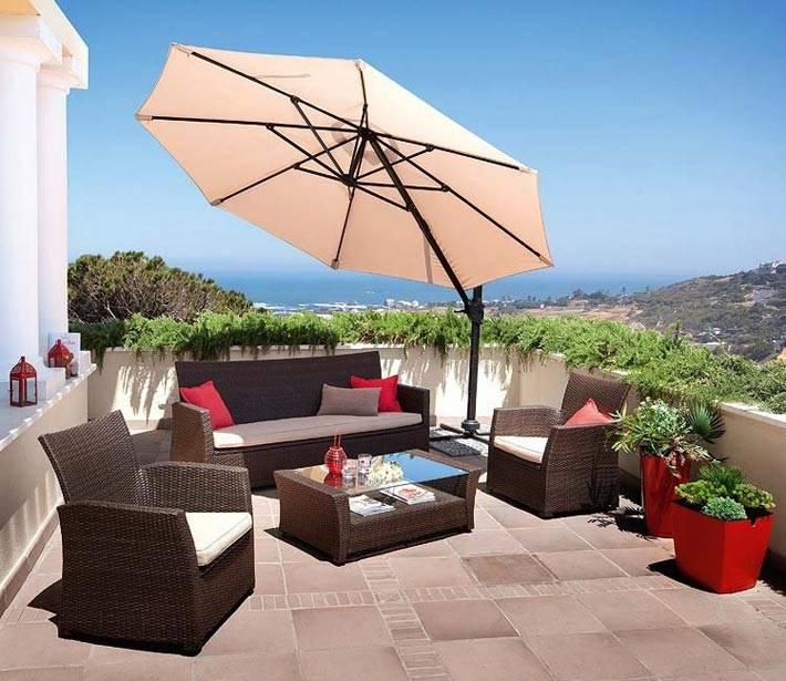 Небольшая терраса на крыше с зонтом и плетеной мебелью