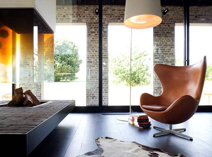 Удобное кожаное кресло-яйцо Egg Chair напротив камина