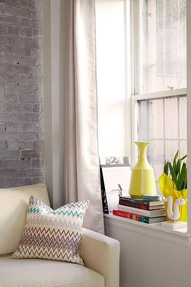 декоративная ваза и яркий живой цветок на белом подоконнике