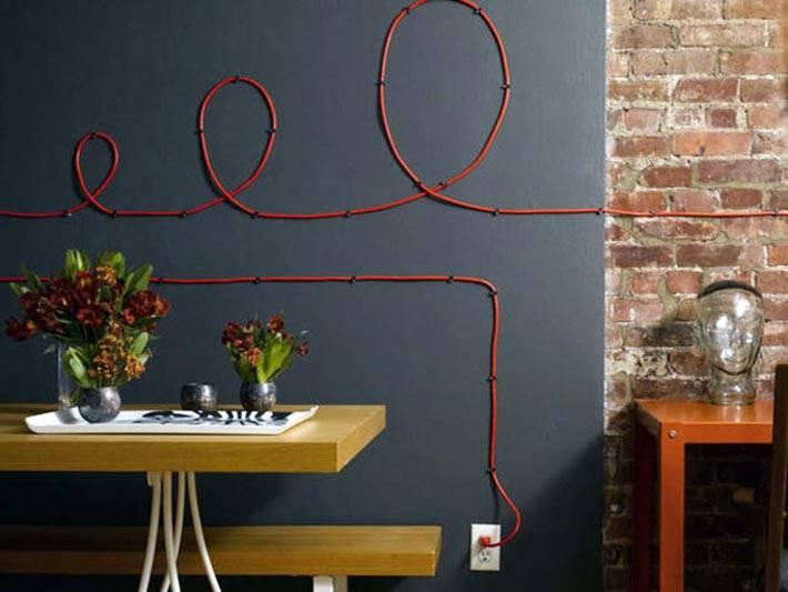 красный провод на черной стене в доме