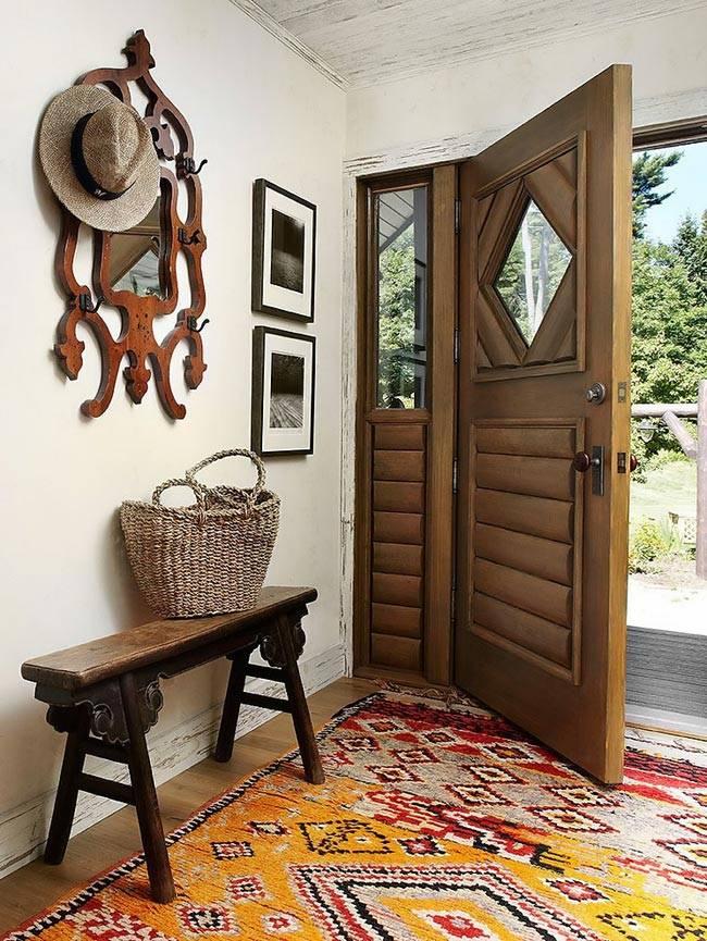Уютная прихожая с ярким пестрым ковром в деревянном доме
