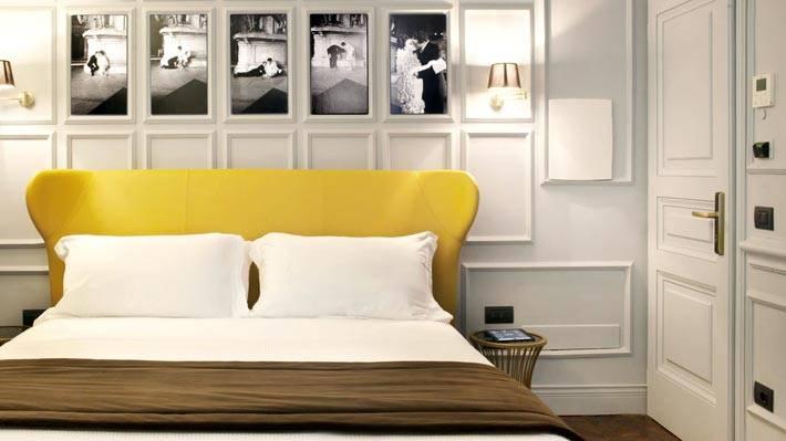 яркое желтое изголовье кровати в черно-белой комнате фото