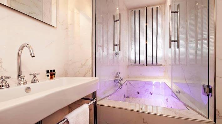 красивый интерьер ванной с мраморной облицовкой и джакузи