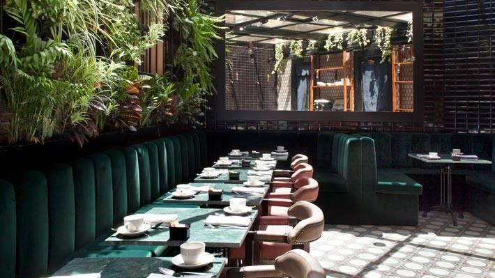 Кофейные столики в ресторане с зелеными бархатными диванами