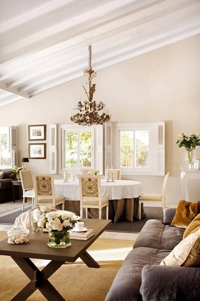 Светлый интерьер гостиной комнаты с вычурной люстрой фото